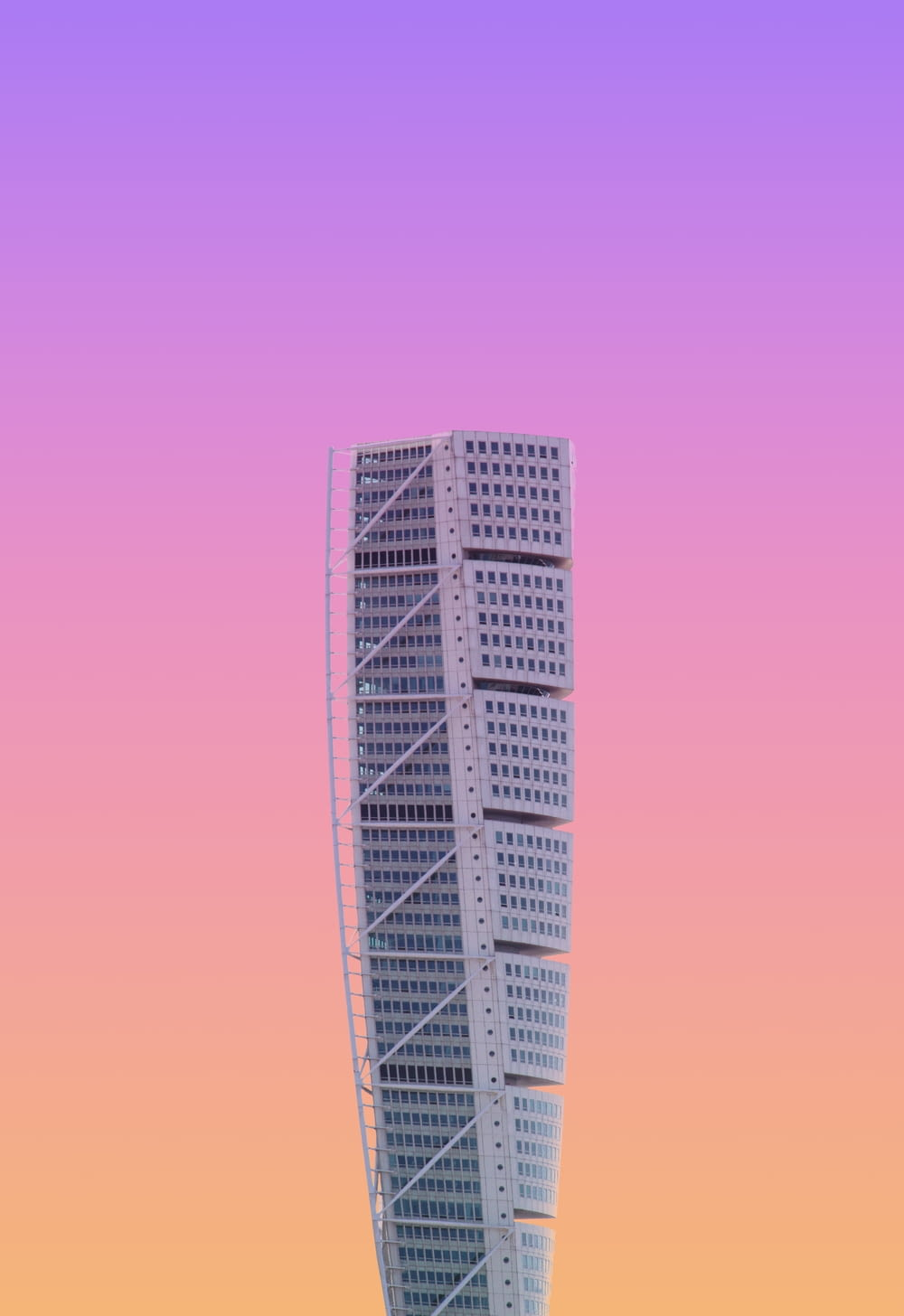 white high-rise building under a purple sky
