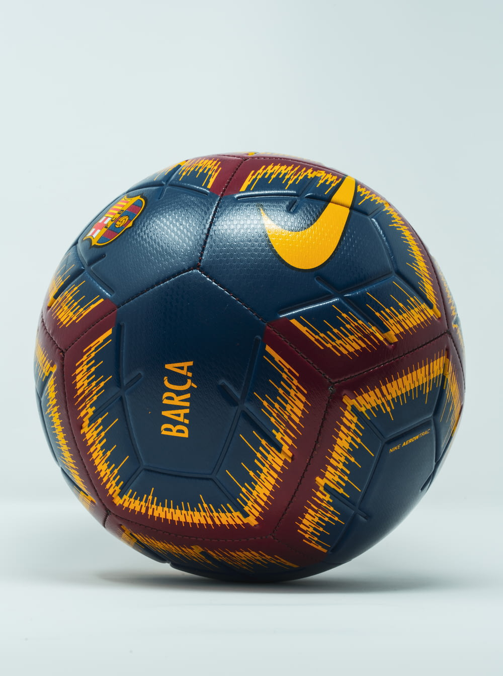 blue, maroon, and yellow Nike soccer ball