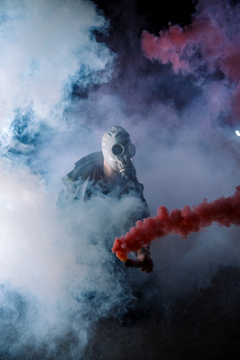 man with gray gas mask standing with gas smokes