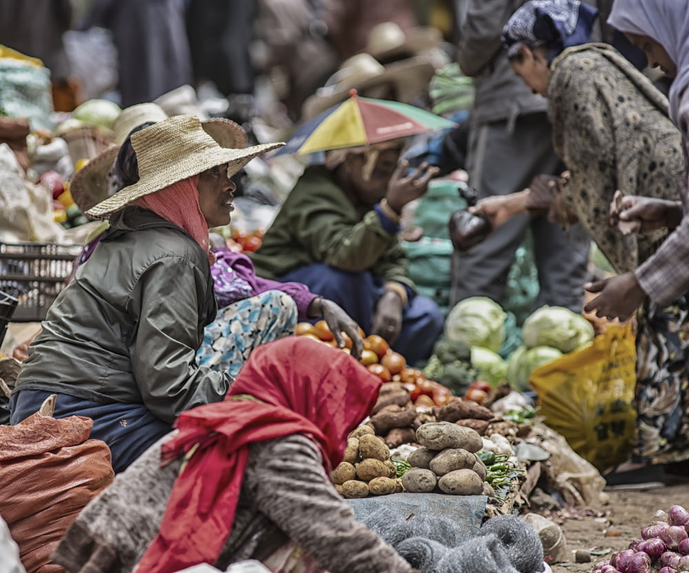 selective focus photography of crowd walking beside displayed vegteables