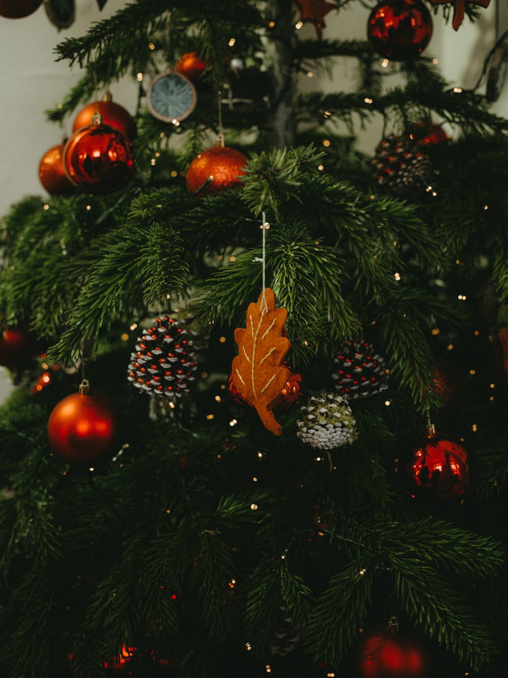 closeup photo of Christmas tree with baubles, pine cones, and string lights