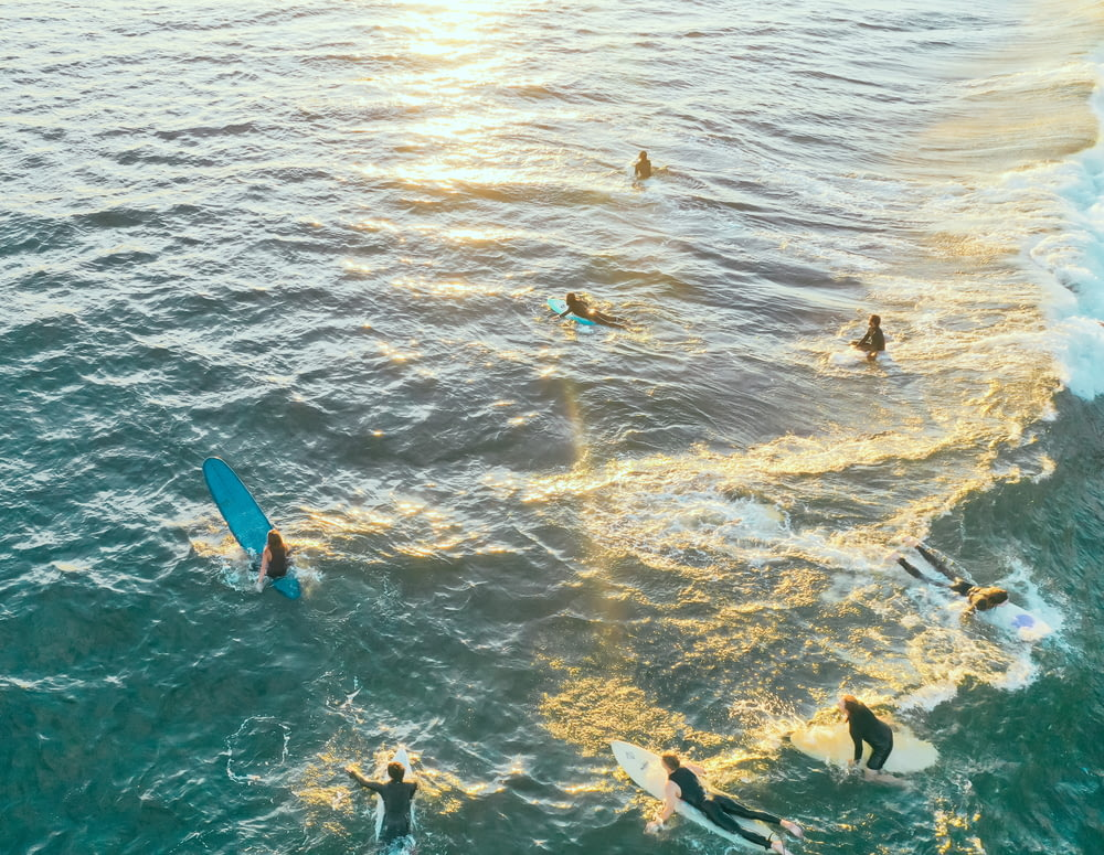 people surfing on ocean at daytime