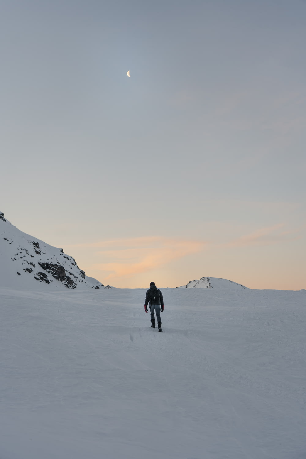 person walking on snow-covered field and mountain during daytime