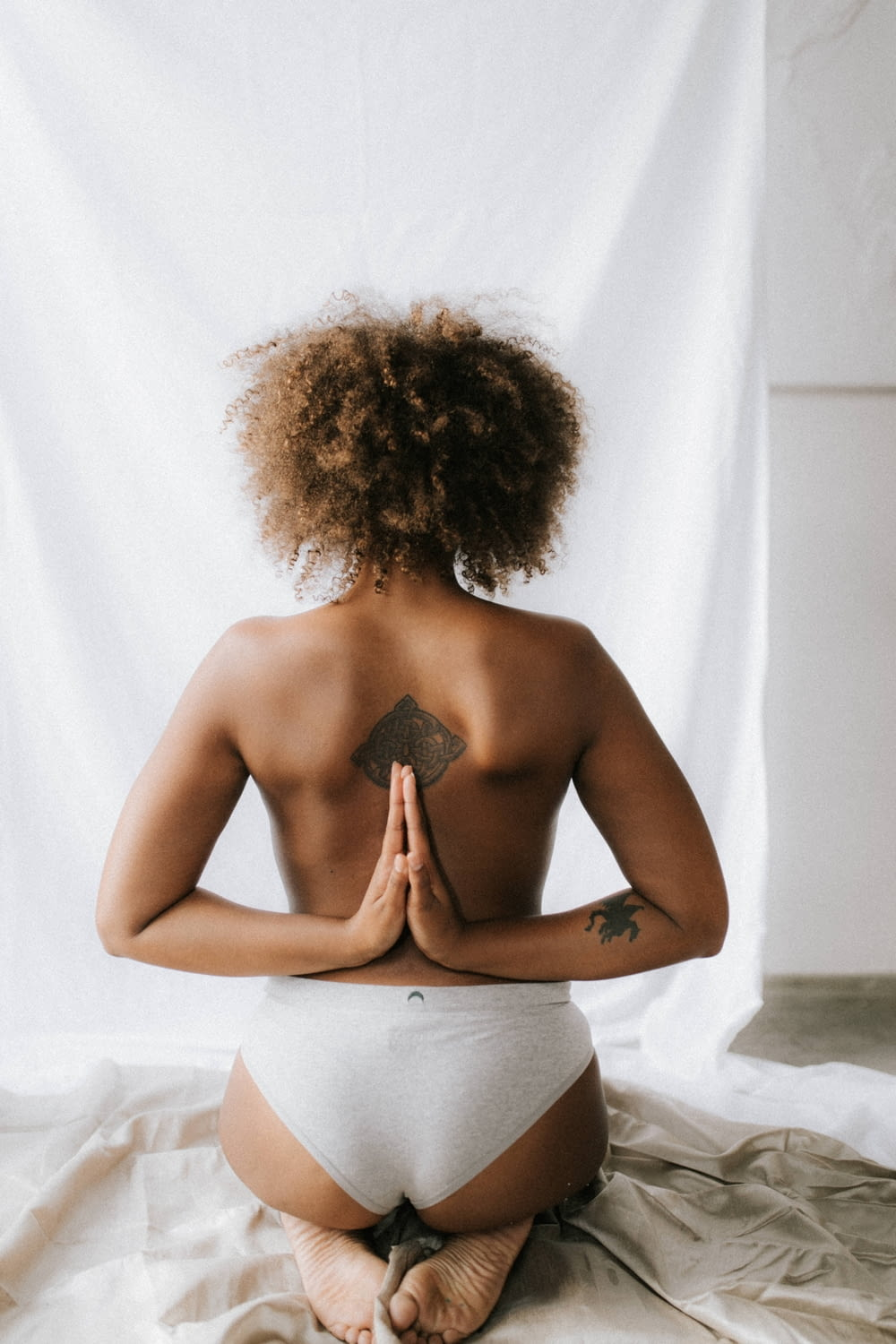 woman kneeling with both hands on her back doing praying gesture