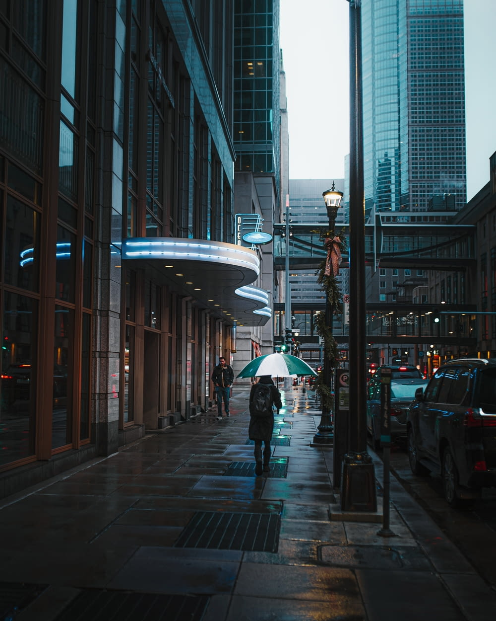 person using umbrella while walking on pathway and different vehicles on road during night time