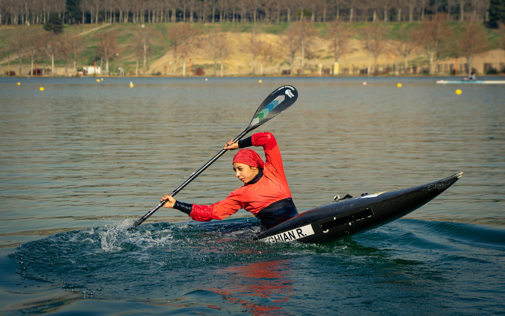 man in red and black jacket riding on black kayak on body of water during daytime