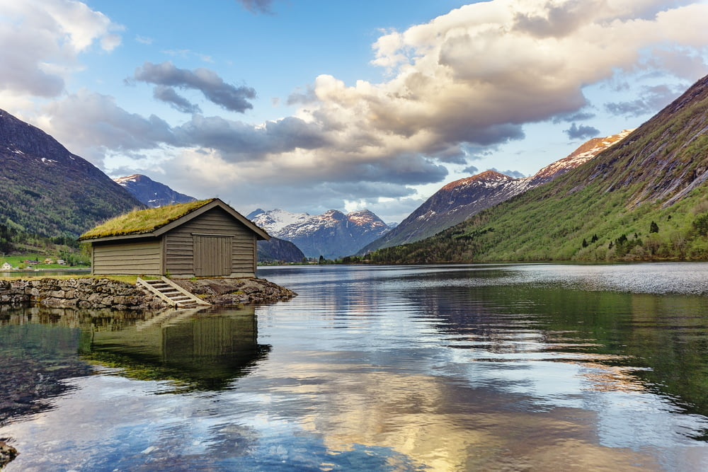 brown wooden house on lake near green mountains under white clouds and blue sky during daytime