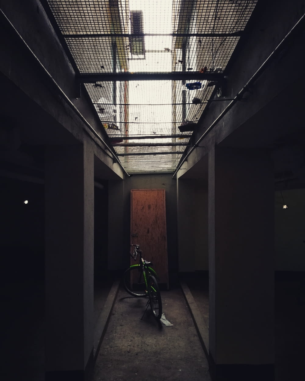 green bicycle parked on hallway
