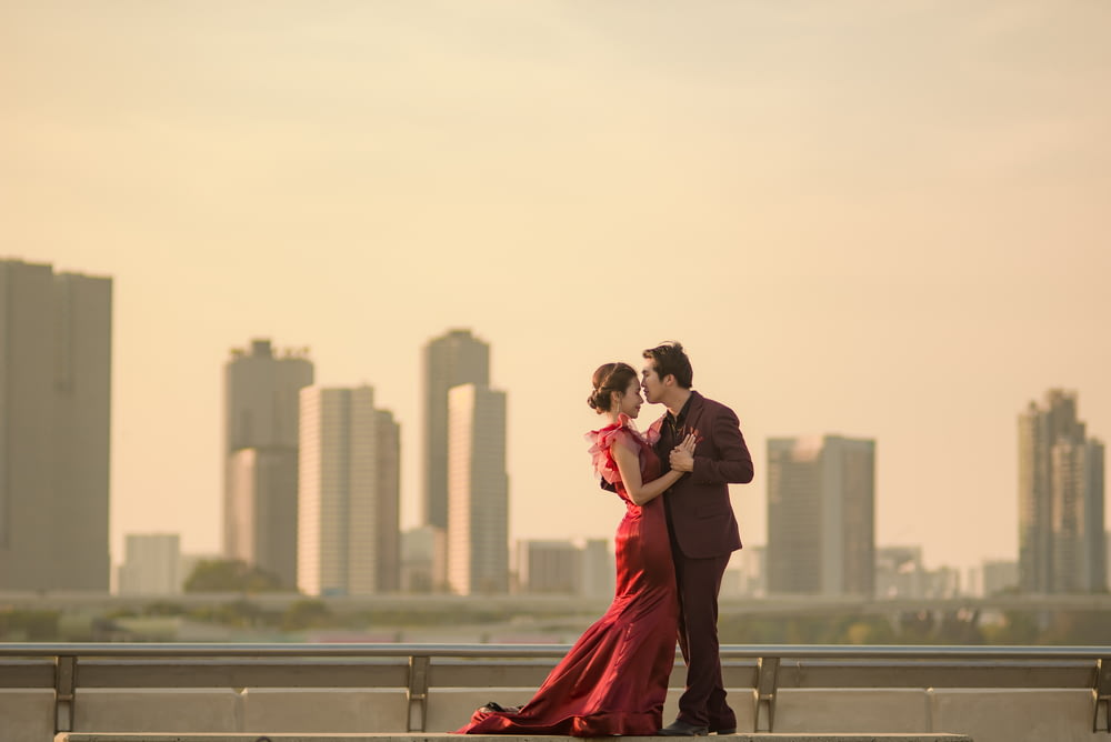 man in black suit kissing woman in red dress on gray metal railings during daytime