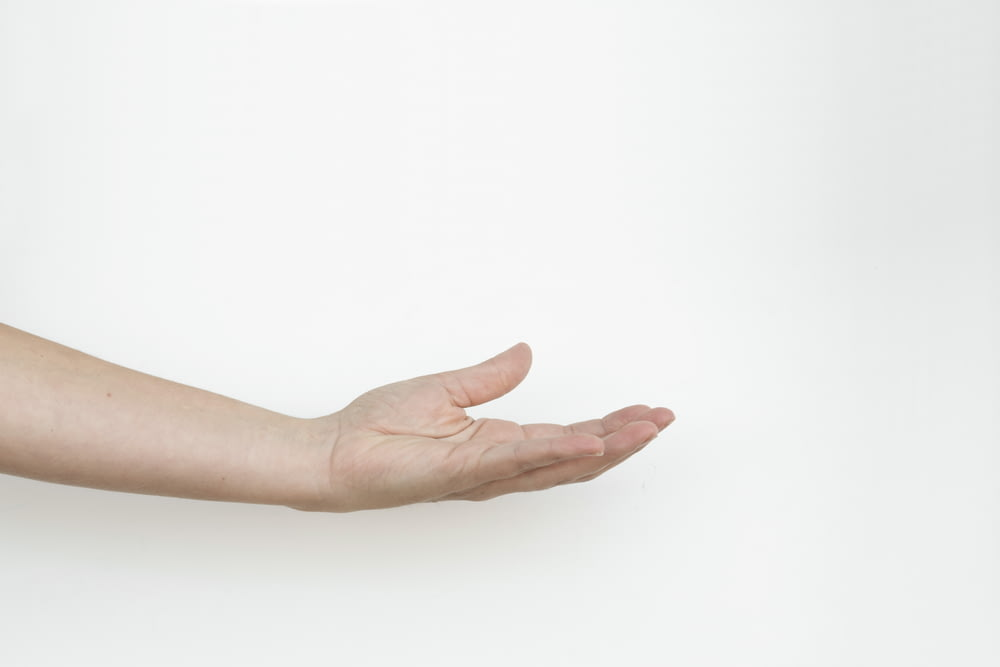 persons hand on white surface