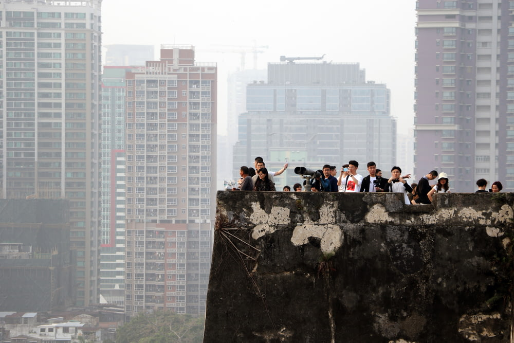 people sitting on rock formation during daytime