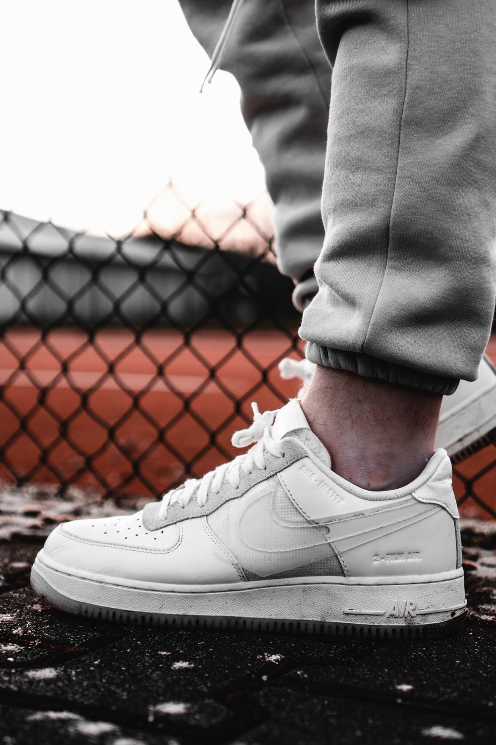 person in gray pants wearing white nike air force 1 low