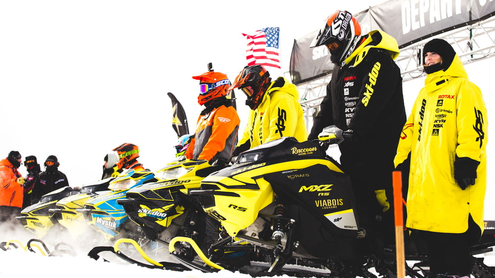 man in black and yellow jacket riding on green and black sports bike