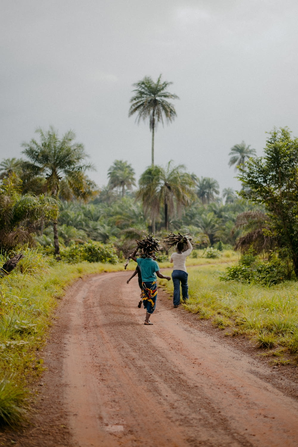 man in blue shirt and black pants walking on dirt road during daytime