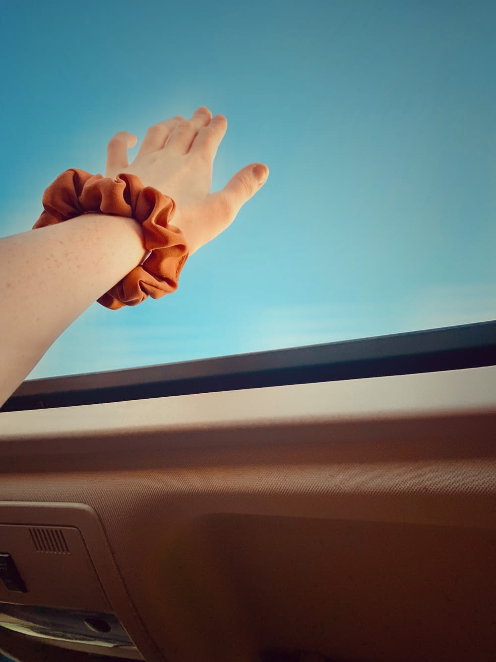 persons left hand on car dashboard