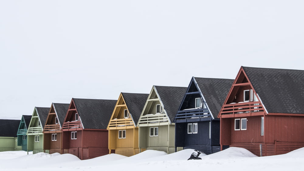 red and brown wooden houses on snow covered ground