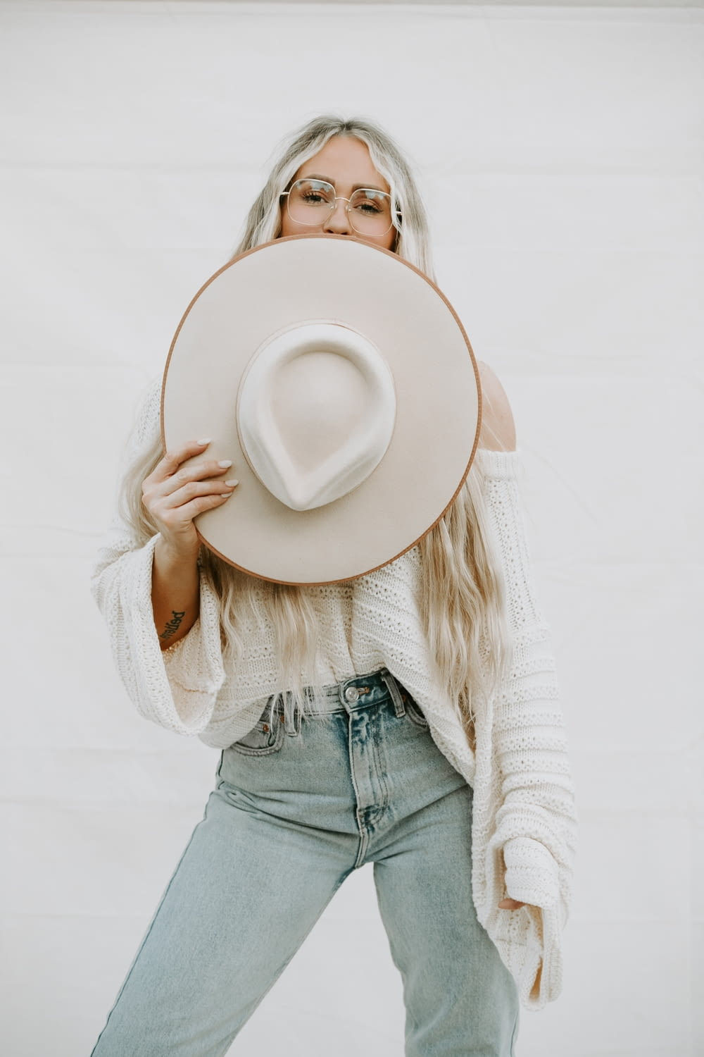 woman in white sweater and blue denim jeans holding white fedora hat