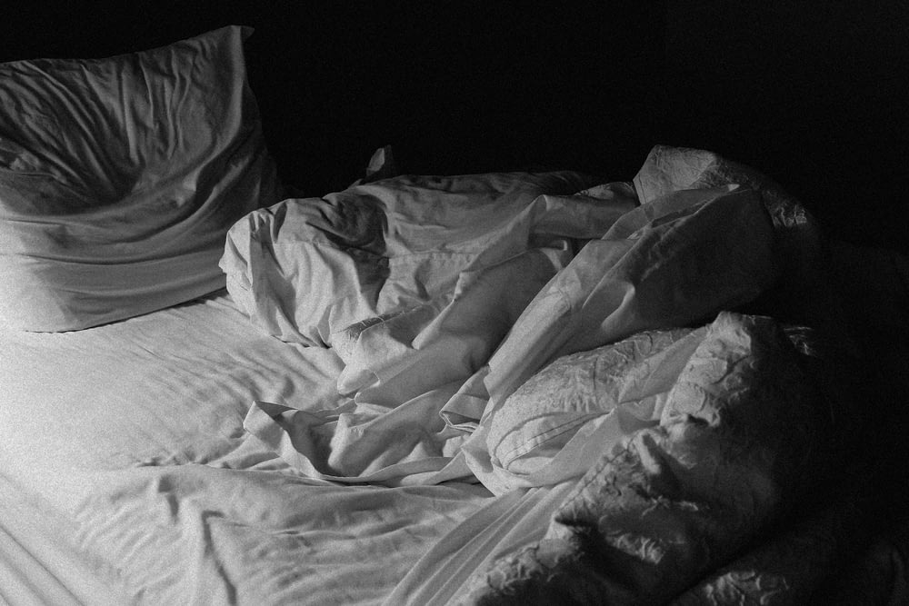 grayscale photo of bed linen