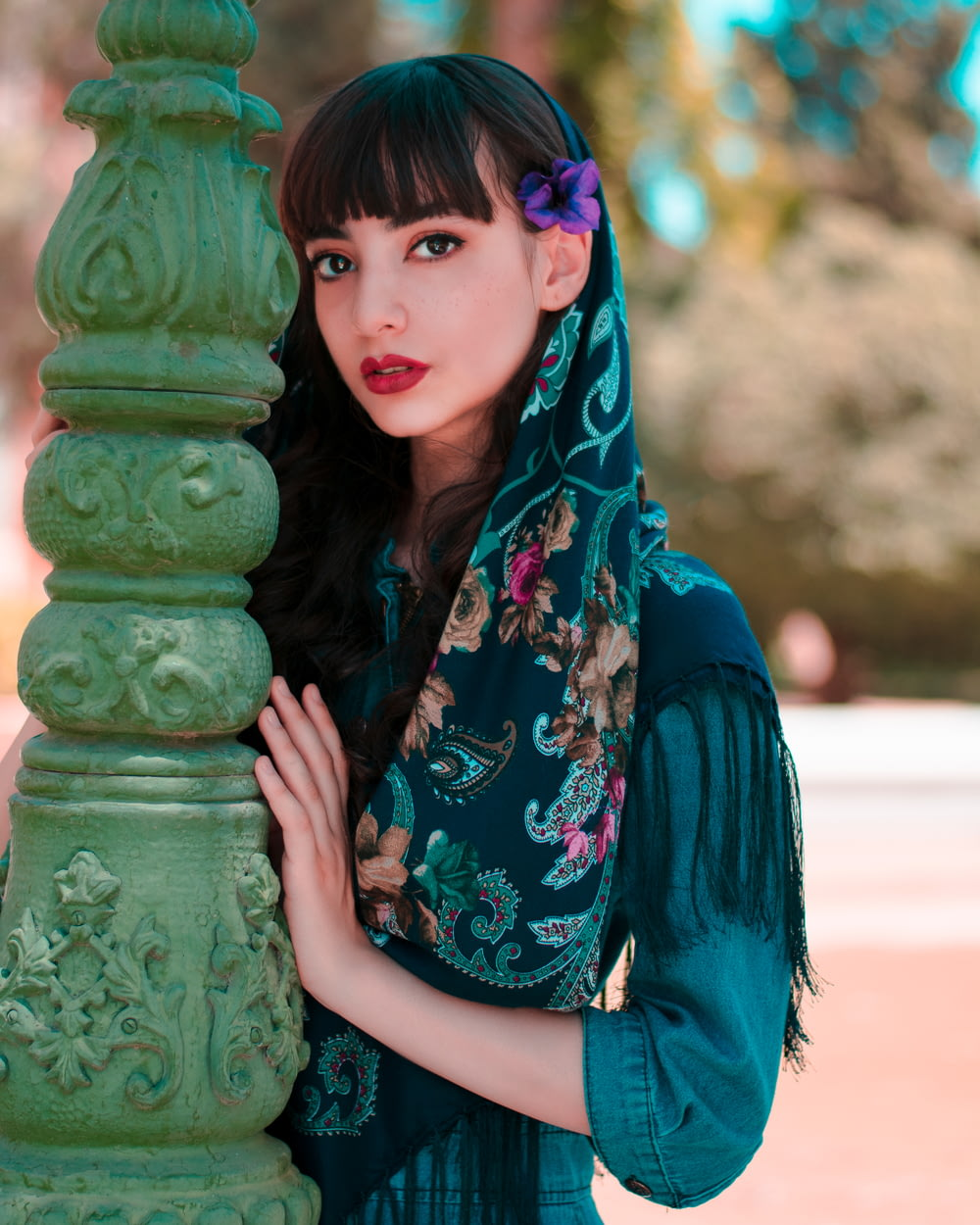 woman in blue and green floral scarf standing beside green concrete post during daytime