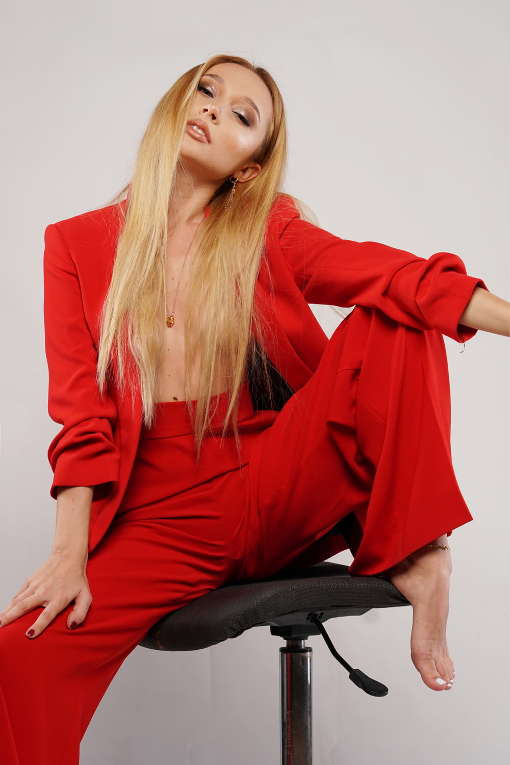 woman in red long sleeve shirt and black pants sitting on black chair