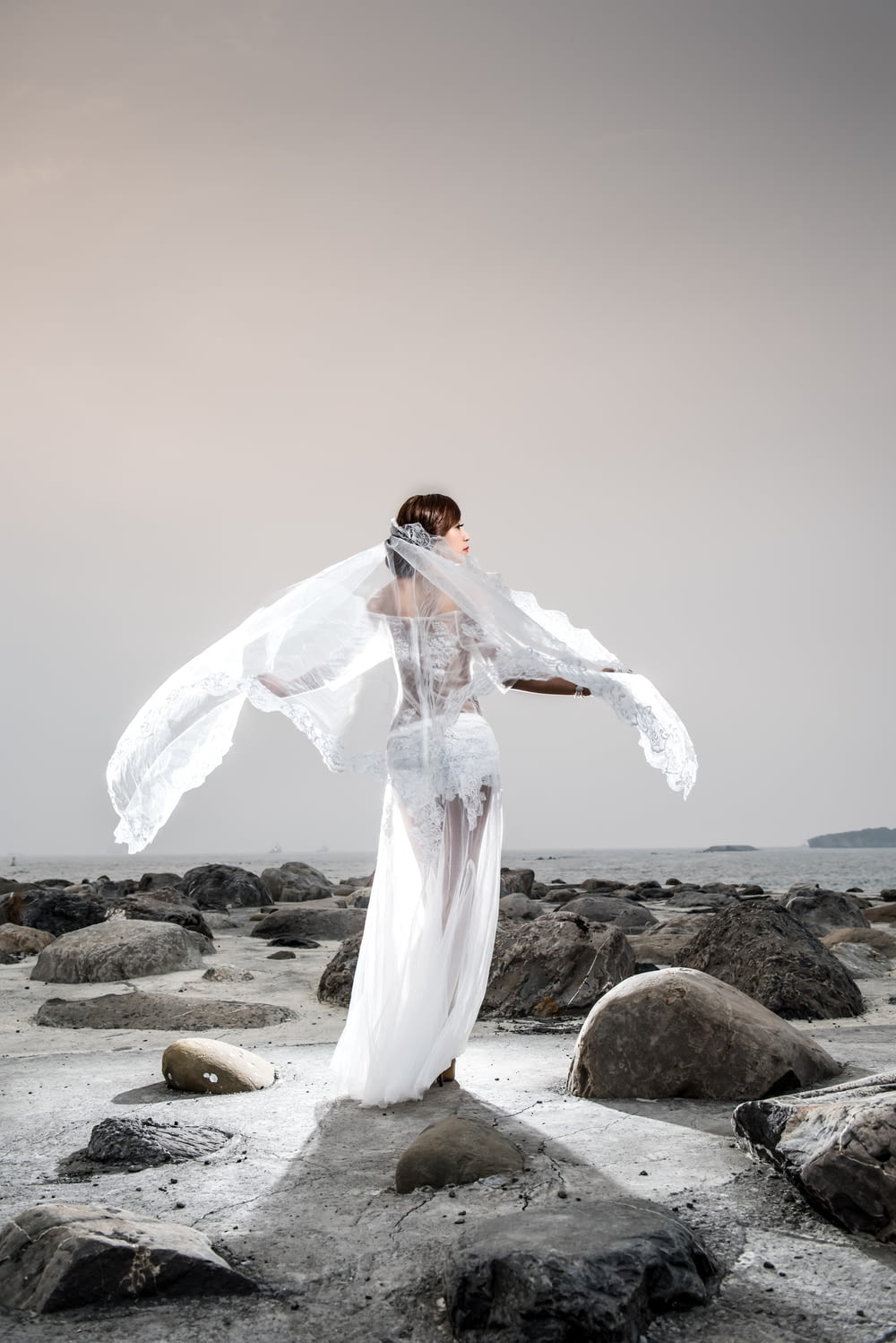 woman in white long sleeve dress standing on rocky shore during daytime