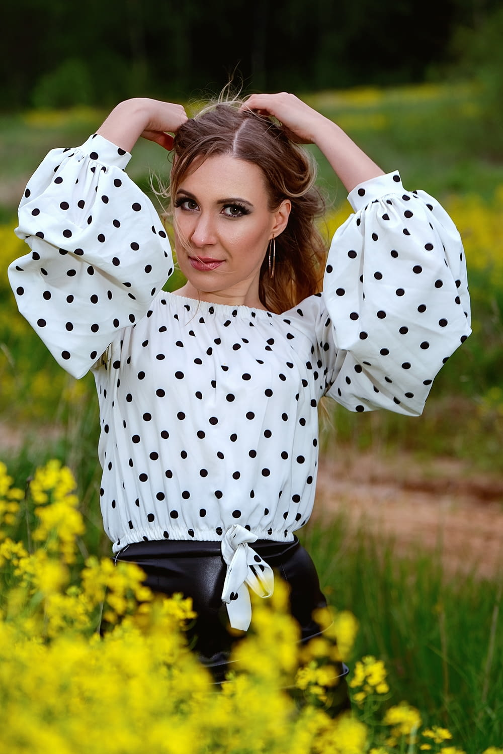 woman in white and black polka dot shirt lying on green grass field during daytime