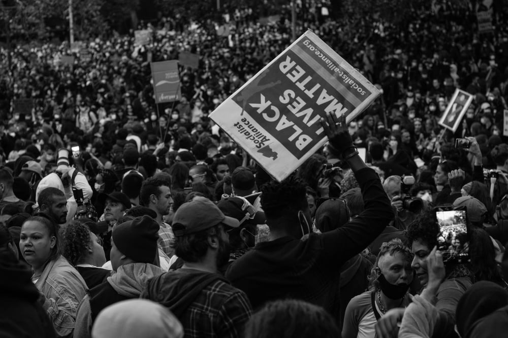 grayscale photo of people holding a signage