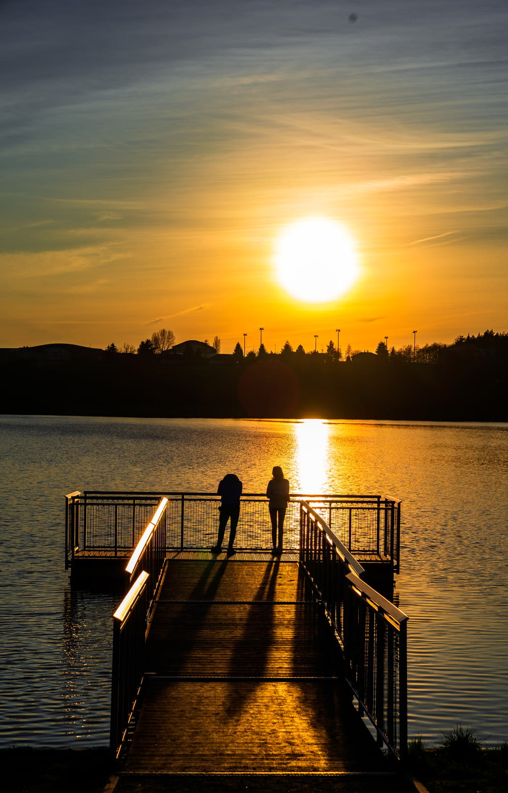 woman in black dress standing on dock during sunset