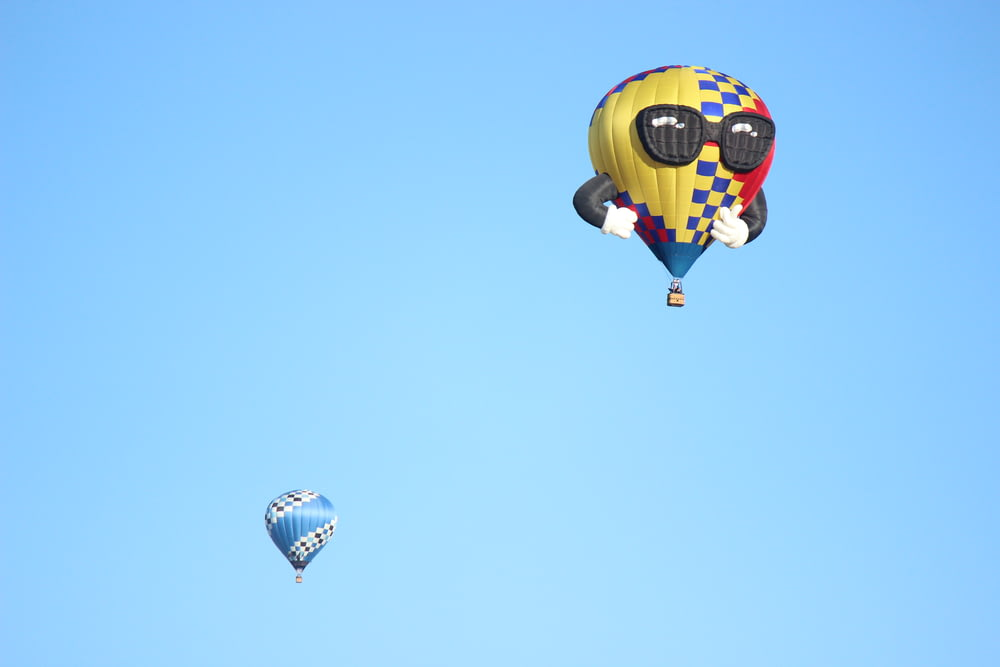 yellow and black hot air balloon in mid air during daytime