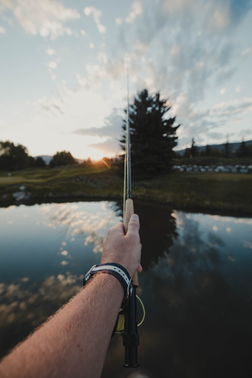 person holding silver and black stick near lake during daytime