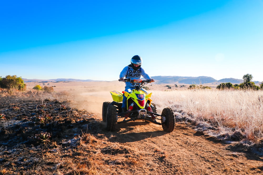 man riding blue and yellow atv on brown field under blue sky during daytime