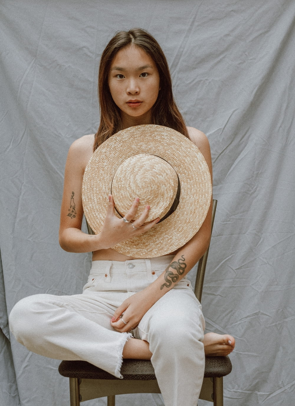 woman in white tank top and white pants wearing brown straw hat
