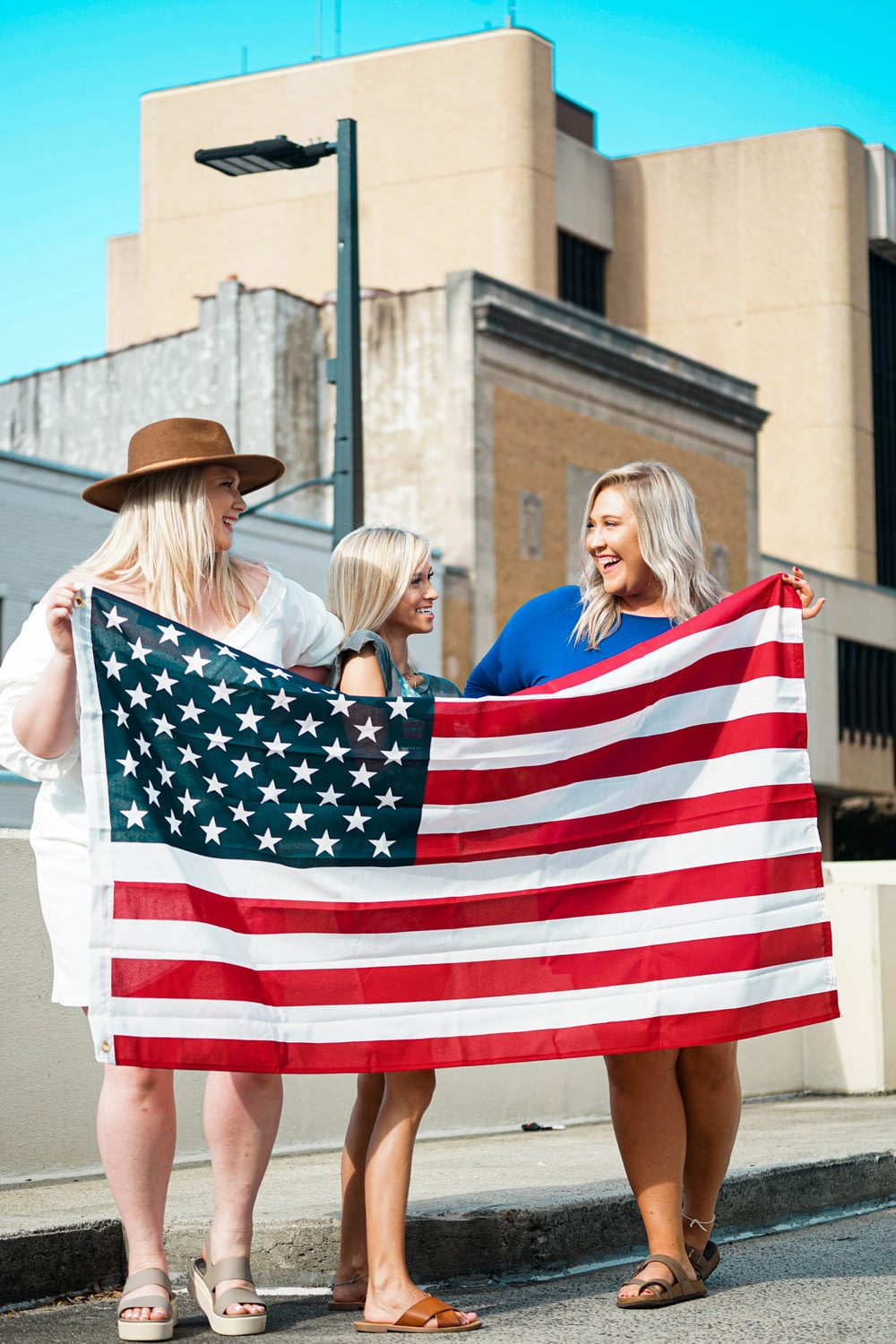 woman in white dress holding us a flag