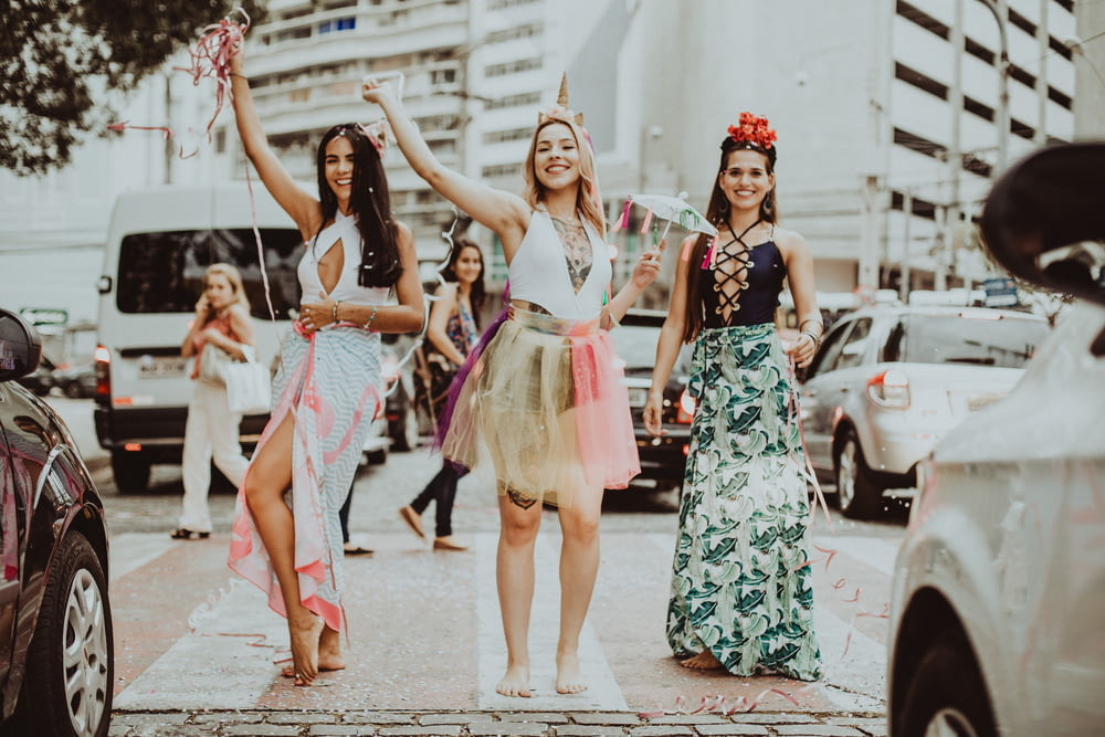 3 women in white and black floral dresses dancing on the street during daytime