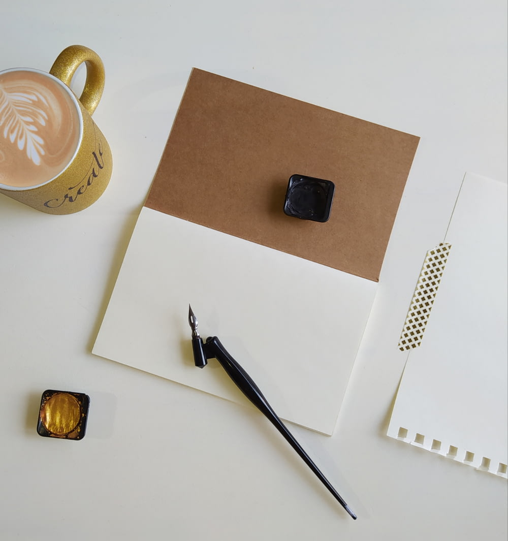 silver and gold watch beside brown ceramic mug on white table