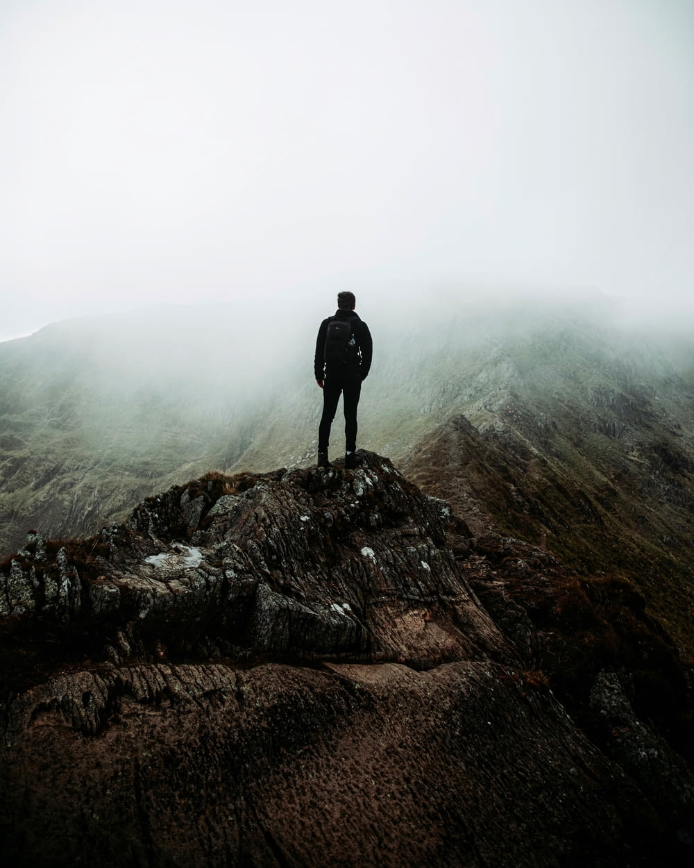 man in black jacket standing on brown rock formation during foggy weather