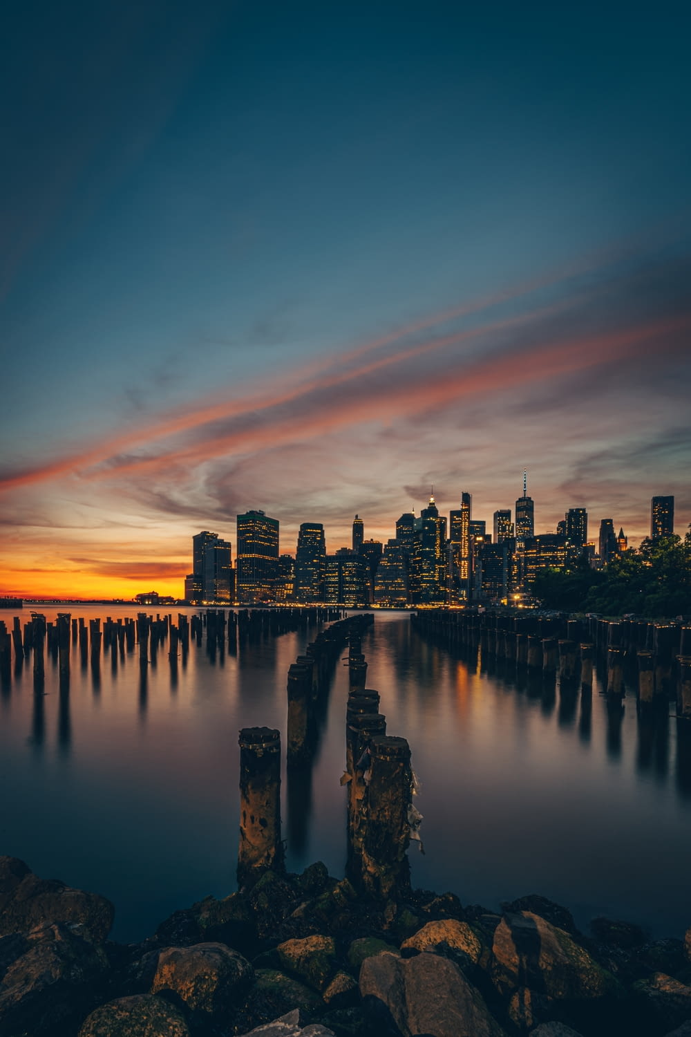 city skyline across body of water during sunset