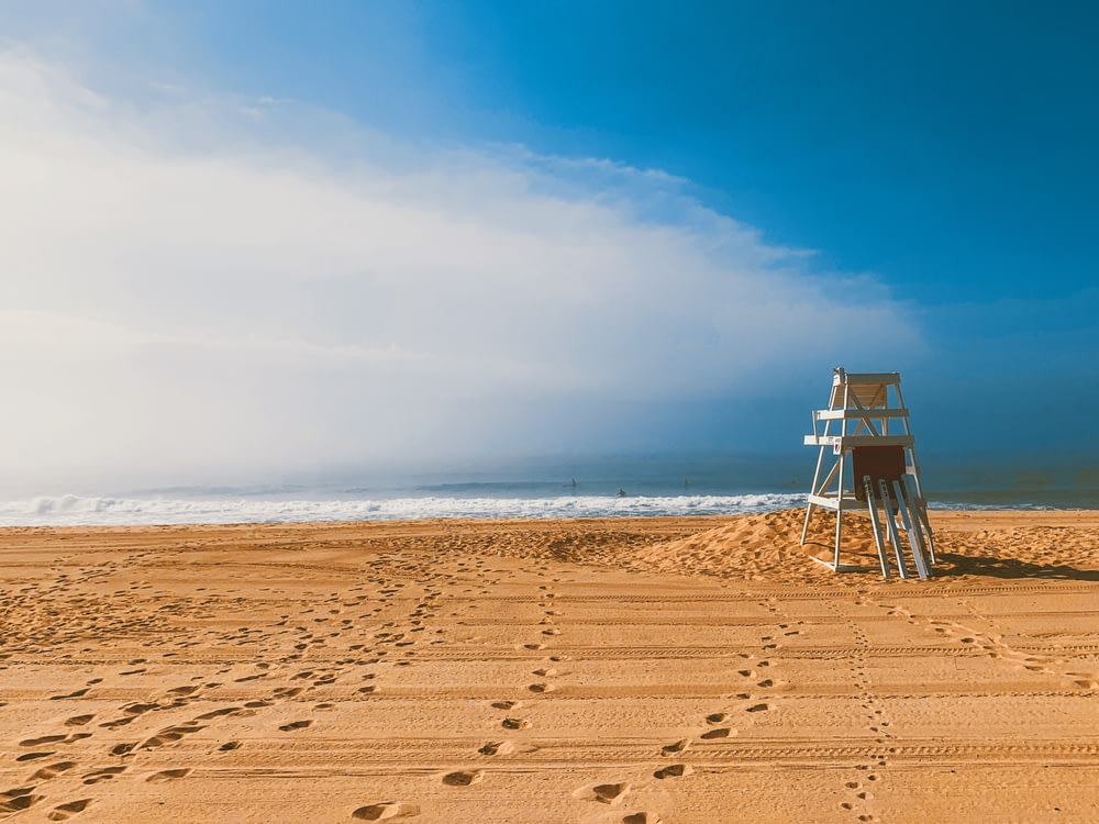 white wooden lifeguard house on beach shore during daytime