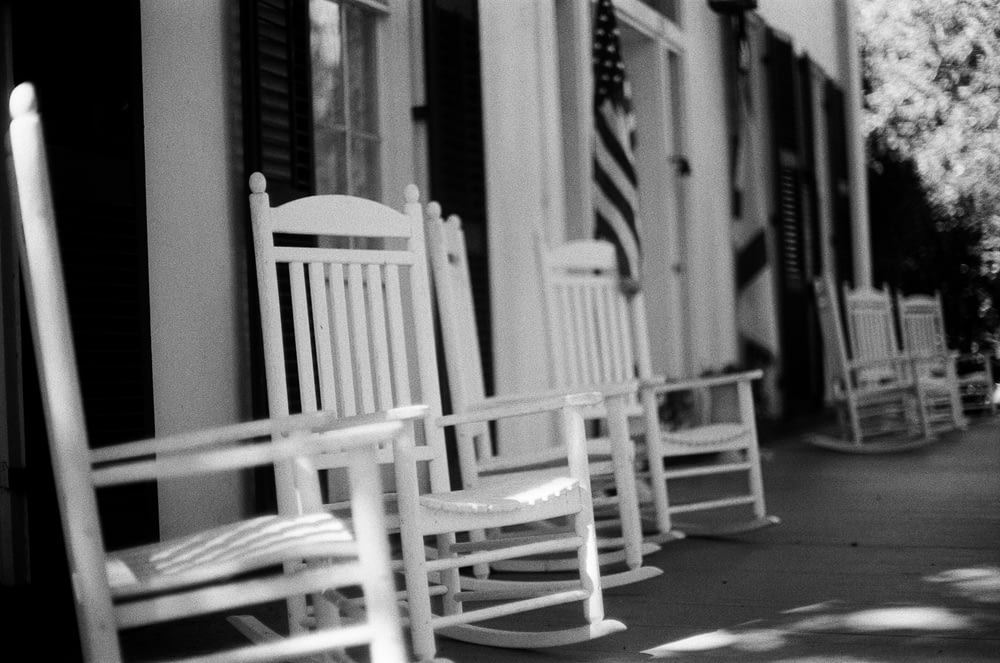grayscale photo of wooden rocking chair