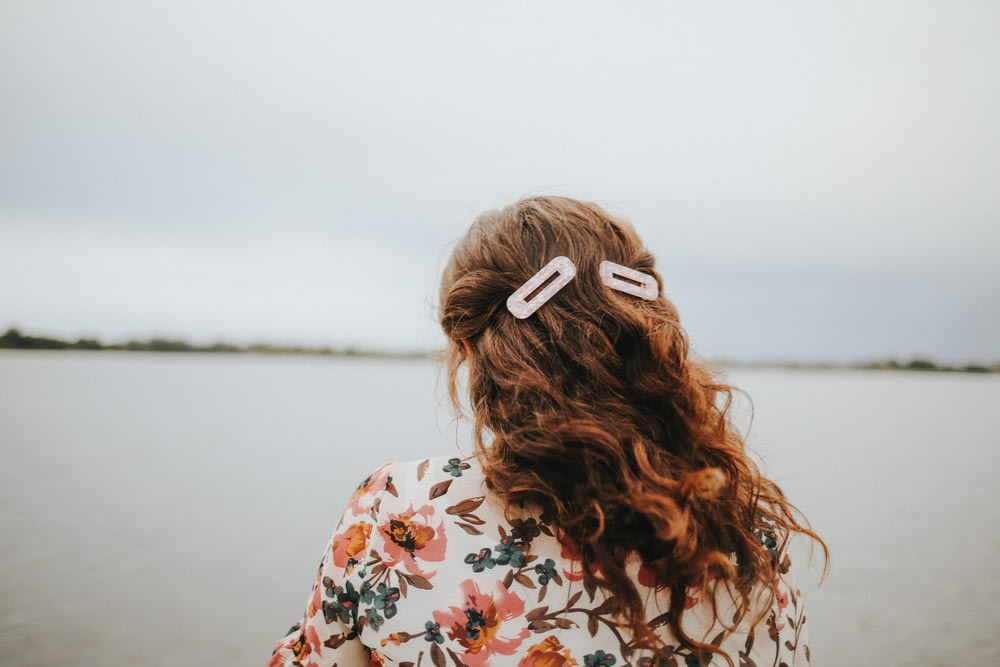 woman in white red and green floral shirt with white and brown hair tie