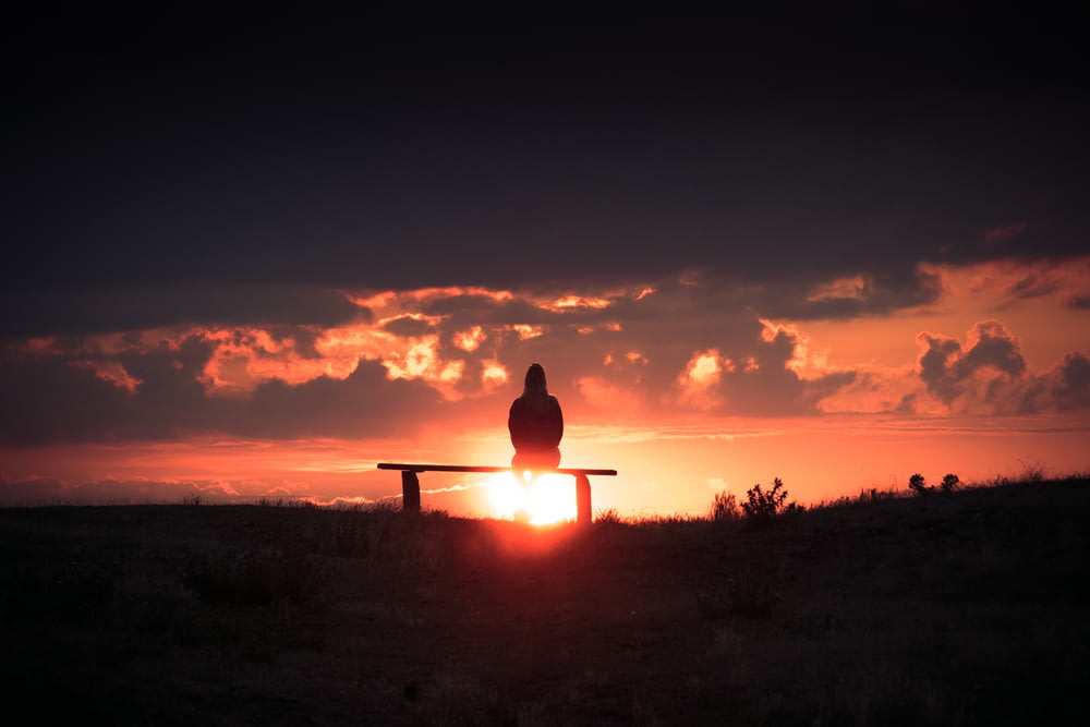 silhouette of person sitting on bench during sunset