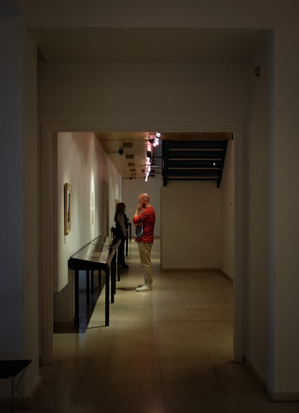 woman in red long sleeve shirt standing on hallway
