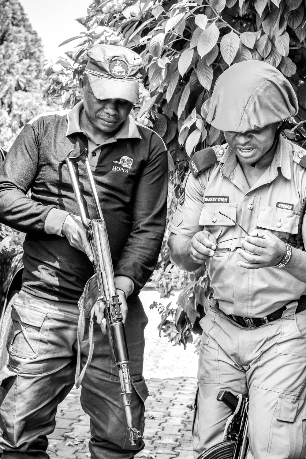 grayscale photo of 2 men in camouflage uniform holding rifle