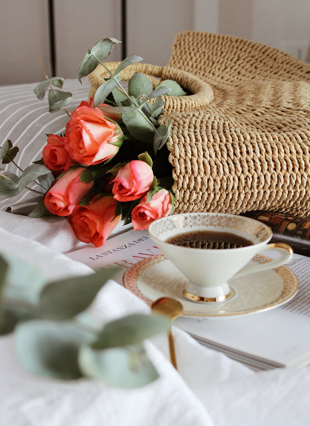 red roses beside white ceramic teacup on white table cloth
