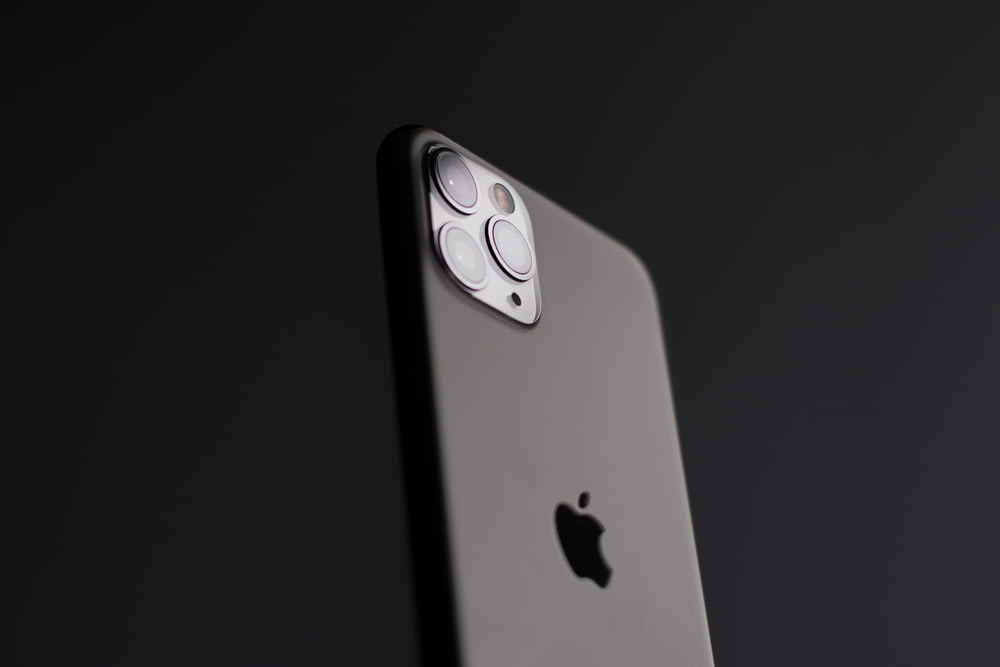 silver iphone 5s on black surface