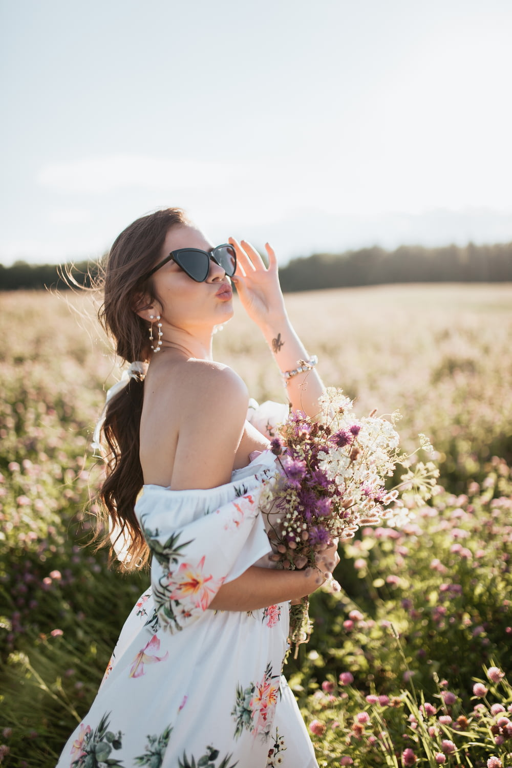woman in white floral tube dress holding purple flowers