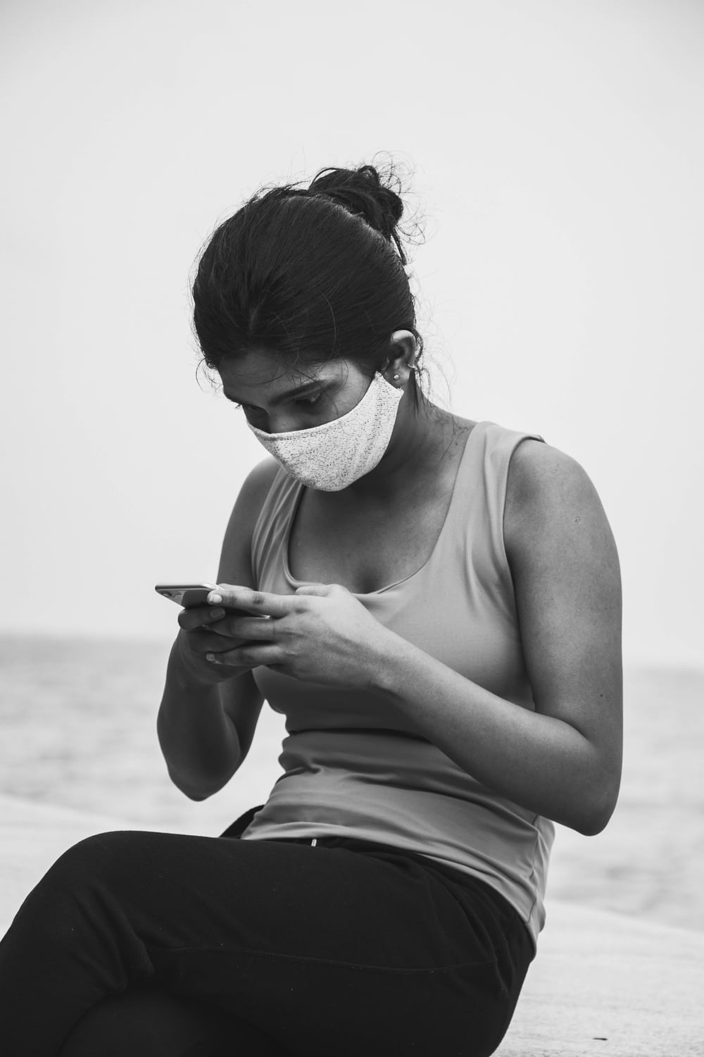 woman in tank top holding smartphone