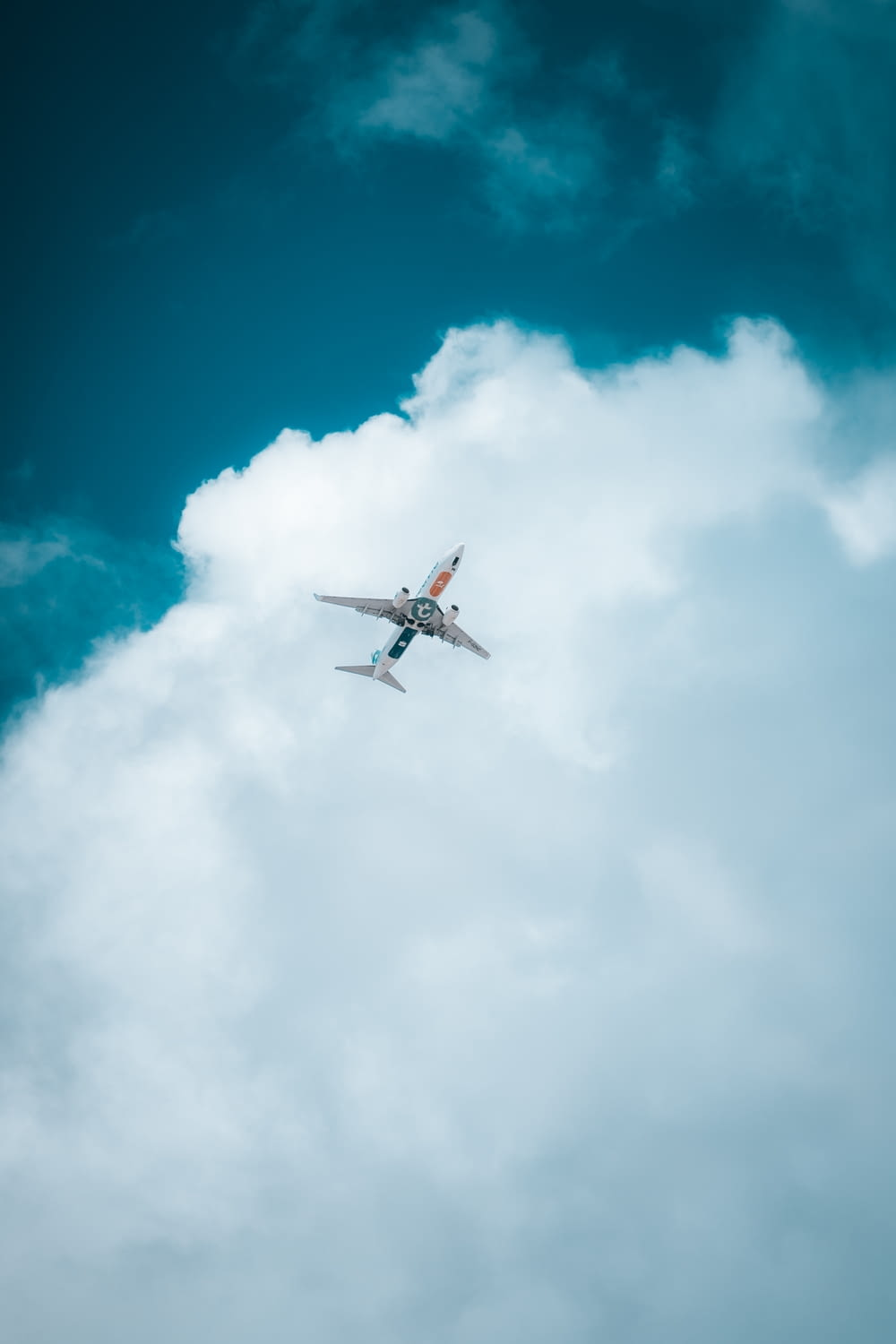 white airplane in mid air under blue sky during daytime