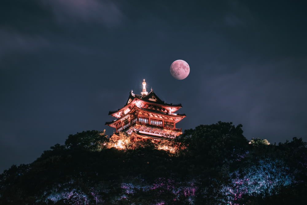 brown and white temple under full moon