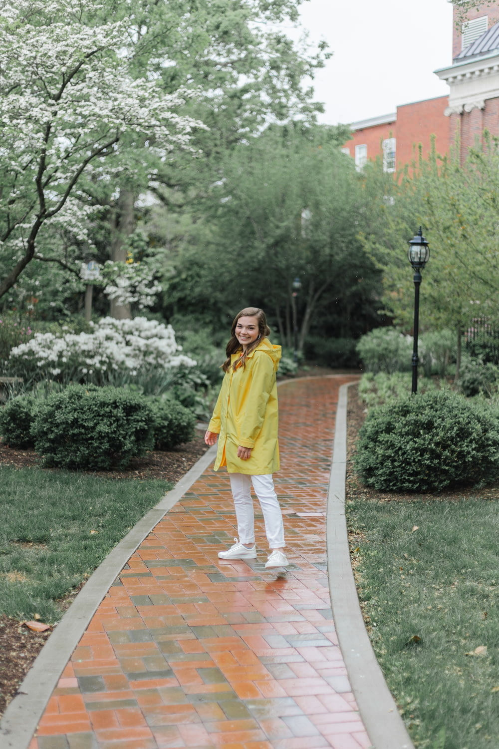 woman in yellow robe standing on brown concrete pathway